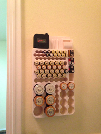 Batteries organized on wall-mounted white shell