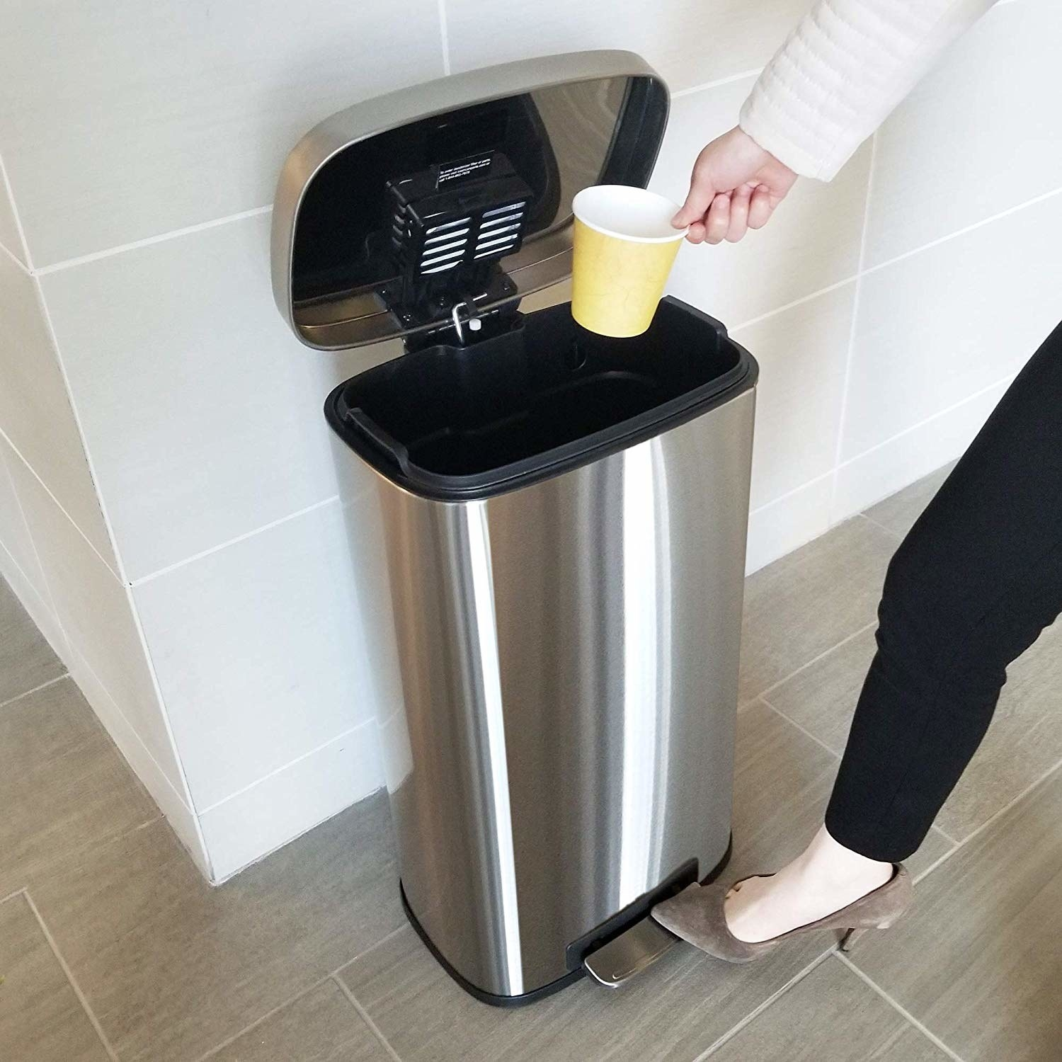 A model stepping on the trashcan opener and throwing out a disposable cup
