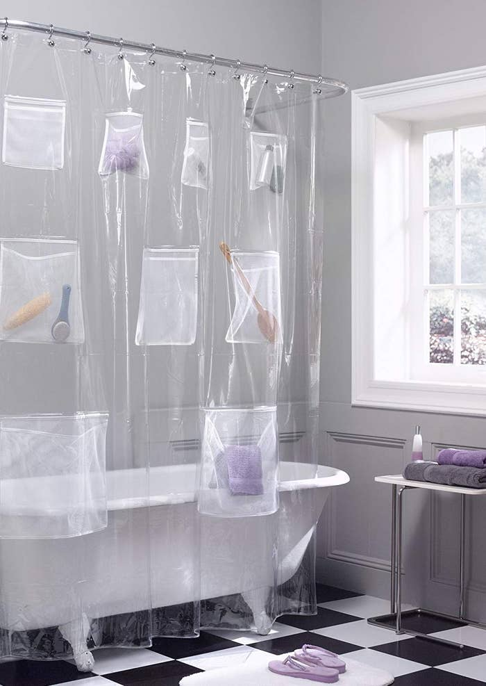Shower curtain liner with pockets containing brushes and grooming products