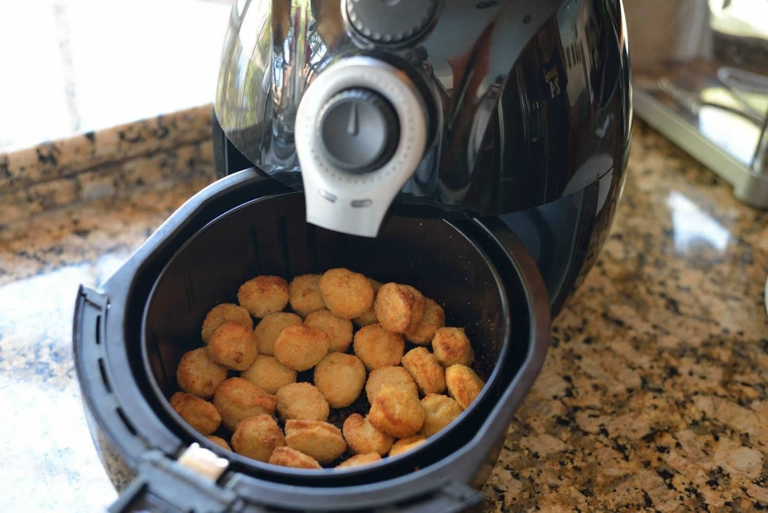 An air fryer with it's pull-out compartment filled with chicken nuggets
