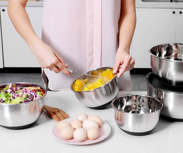 A model whisking eggs in one of the bowls, with other ingredients in the others