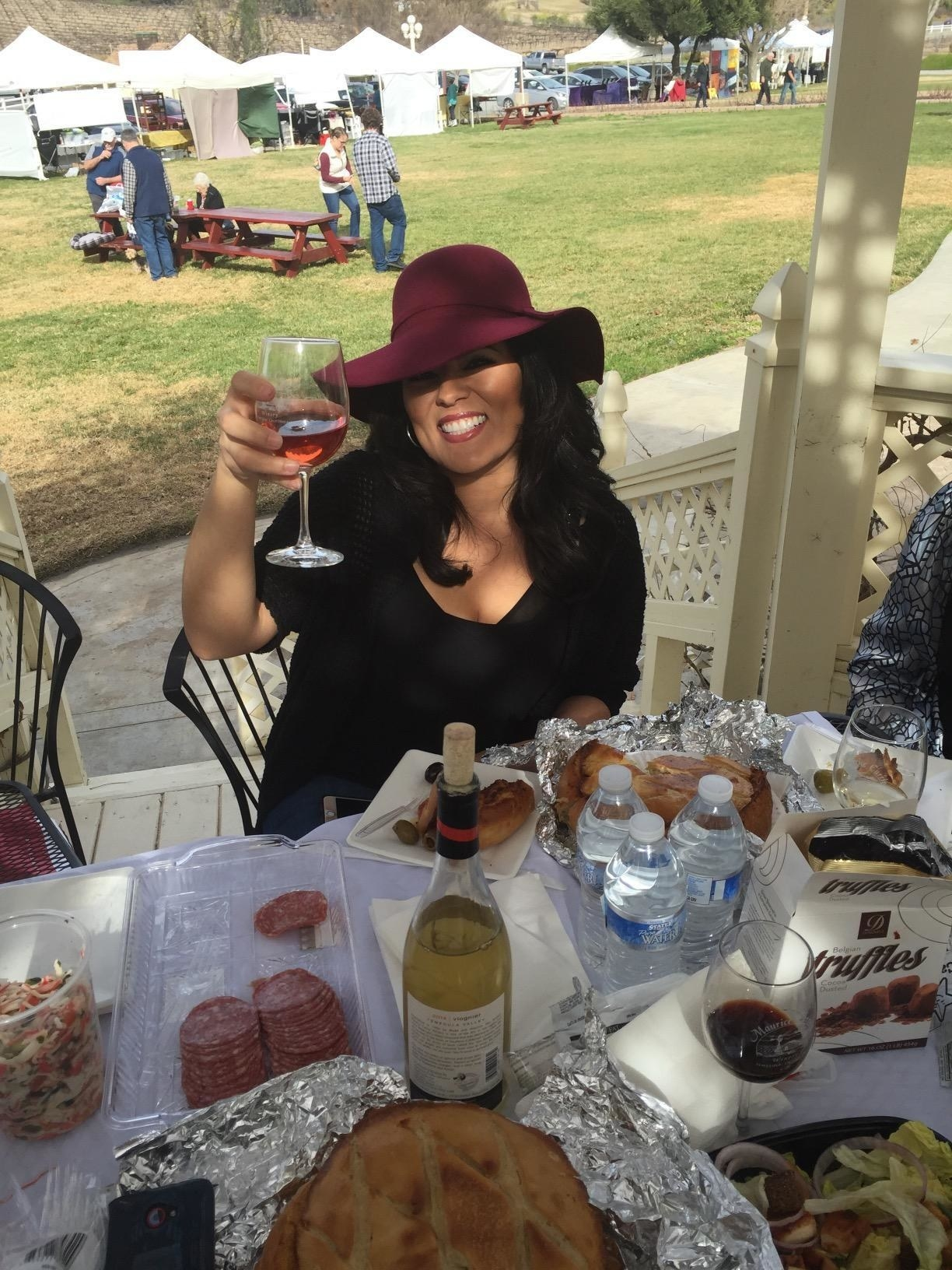 reviewer at a wine tasting wearing the burdundy hat