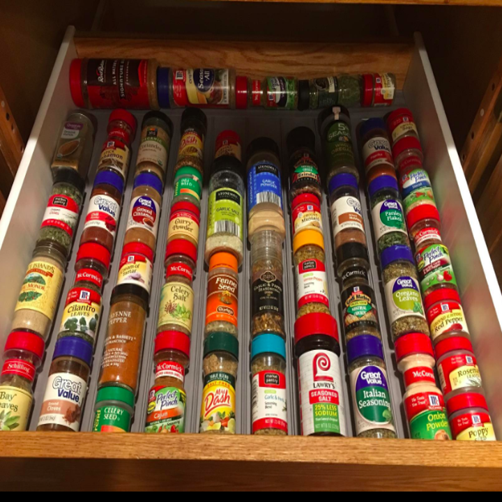 Reviewer's now organized spice drawer showing the bottles stacked in perfectly straight lines thanks to the grooves of the drawer liner