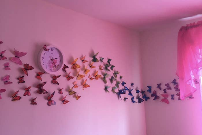 A pink wall with a line of 3D butterflies that look like they're flying by the wall.