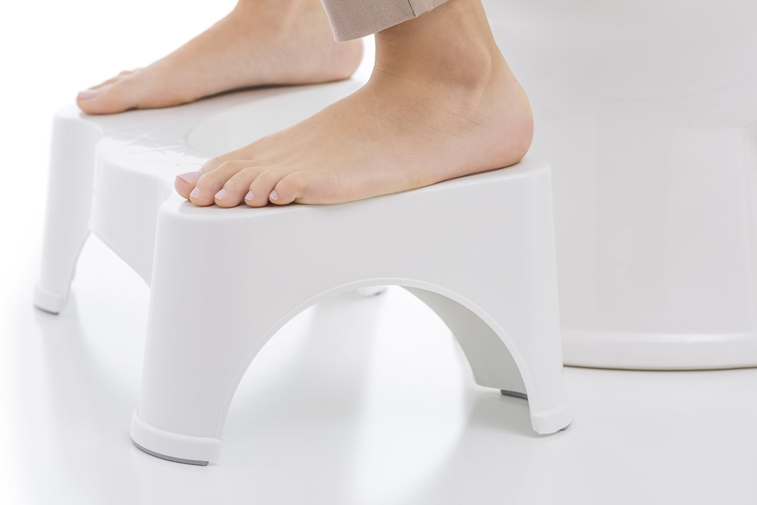 close up of feet perched on top of the squatty potty