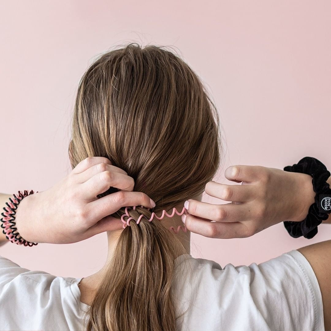 A model ties up their hair with the plastic hair tie, which looks like a thin, coiled landline telephone cord