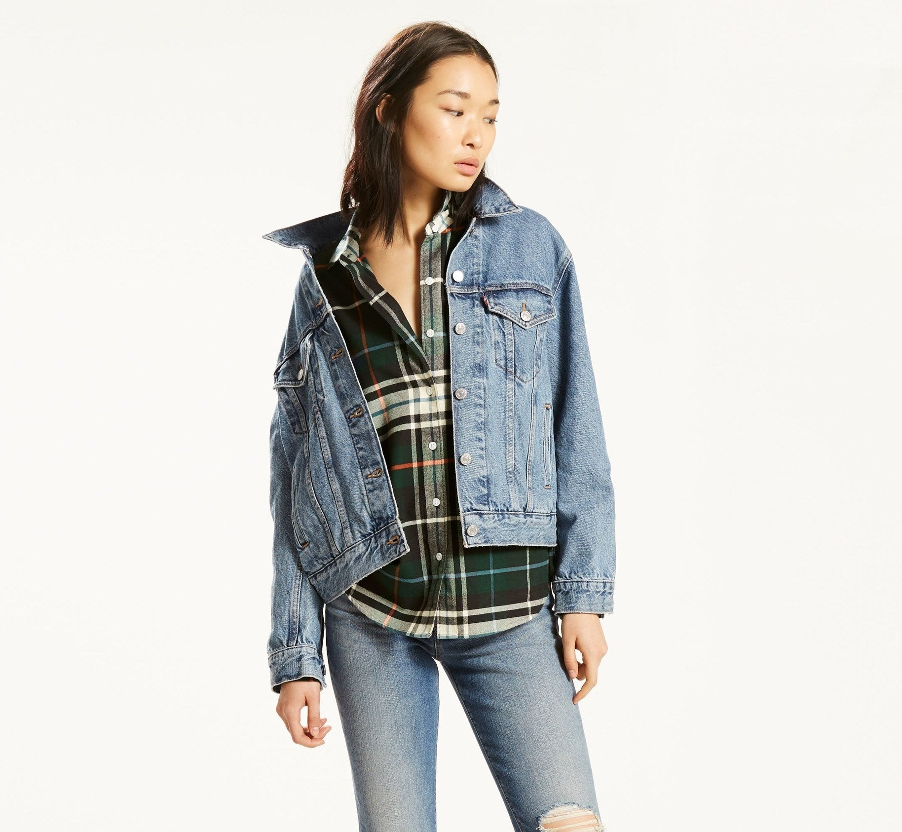 Loose fitting classic denim jacket over plaid shirt and jeans
