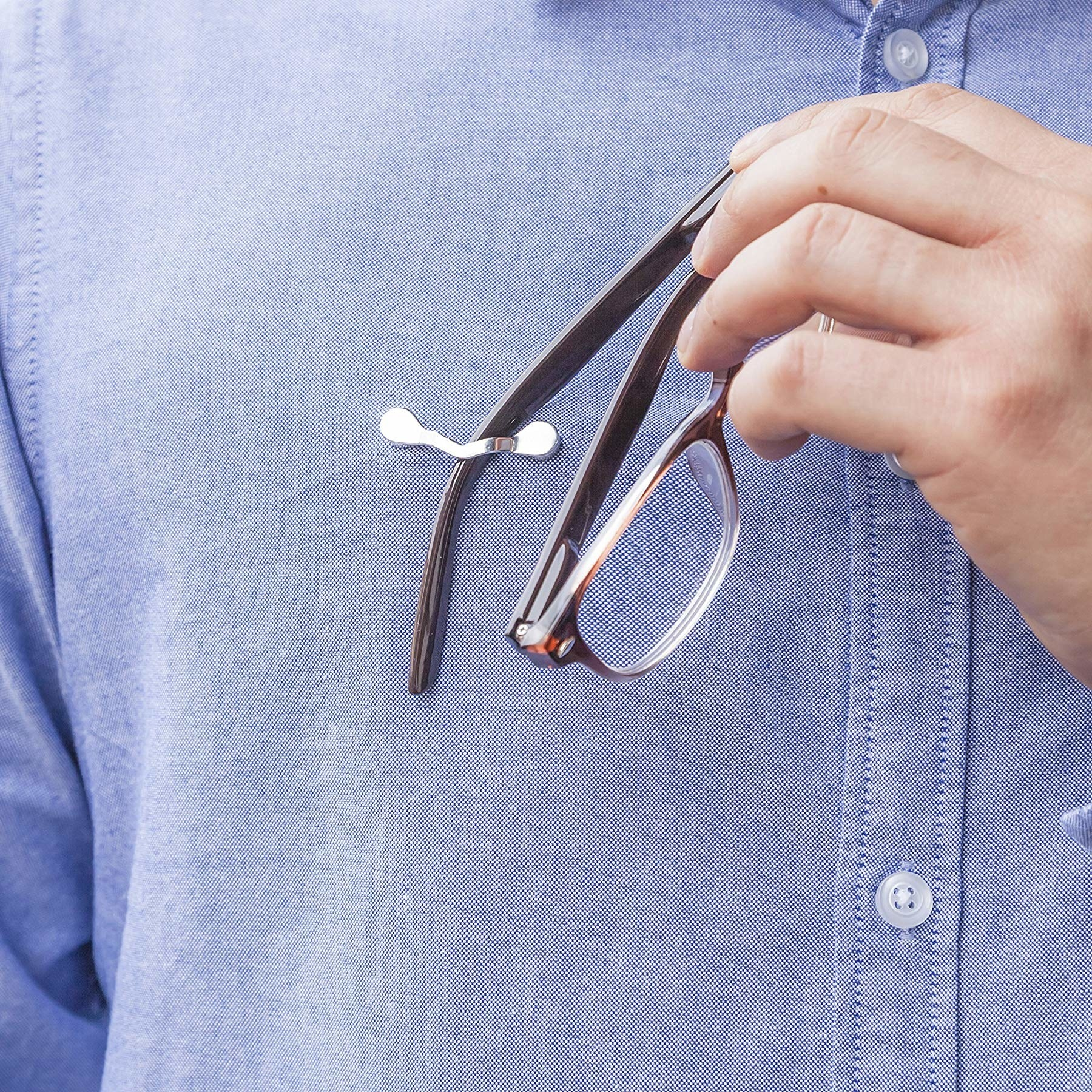 close up of a model placing their glasses into the readerest magnetic eyeglass holder on their shirt