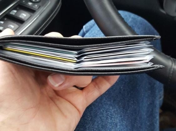 Reviewer's picture of the thin wallet with multiple pages of plastic card slots