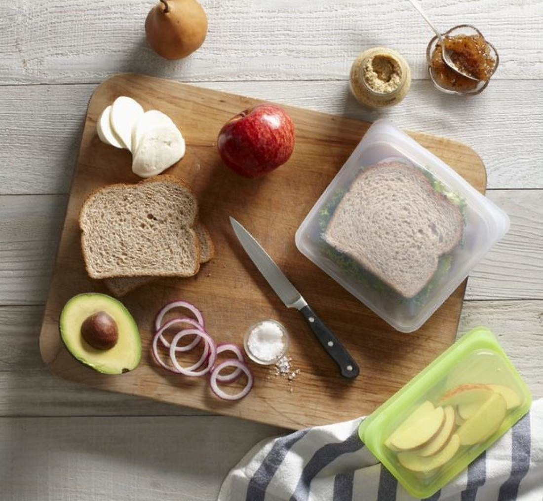 a sandwich spread on top of a cutting board as well as a sandwich inside of a stasher silicone food bag