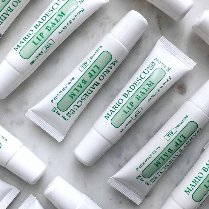 """several white plastic tubes labeled """"Mario Badescu lip balm"""" in green font"""