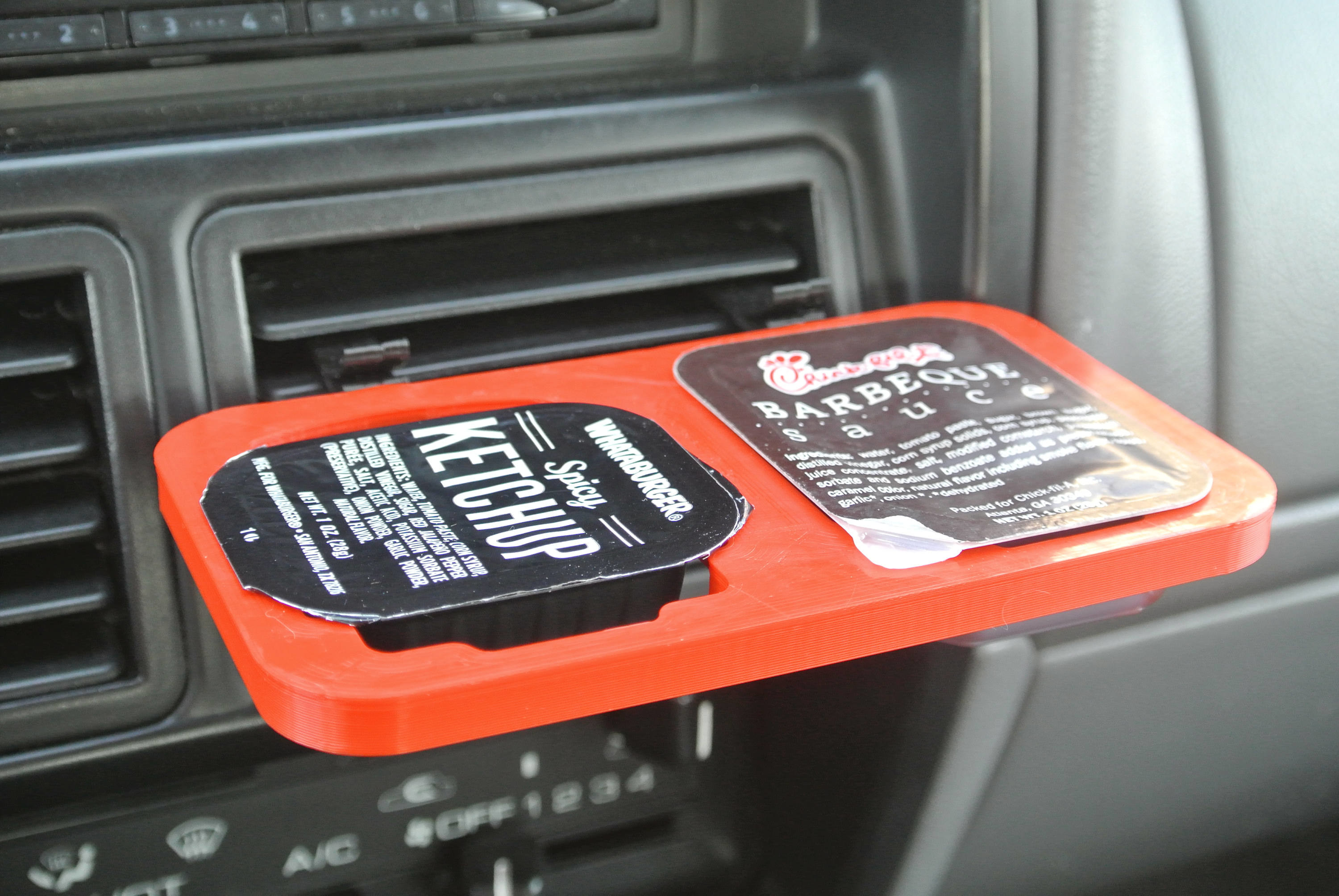 A red flat container with two holes for dipping sauce is clipped to a car vent