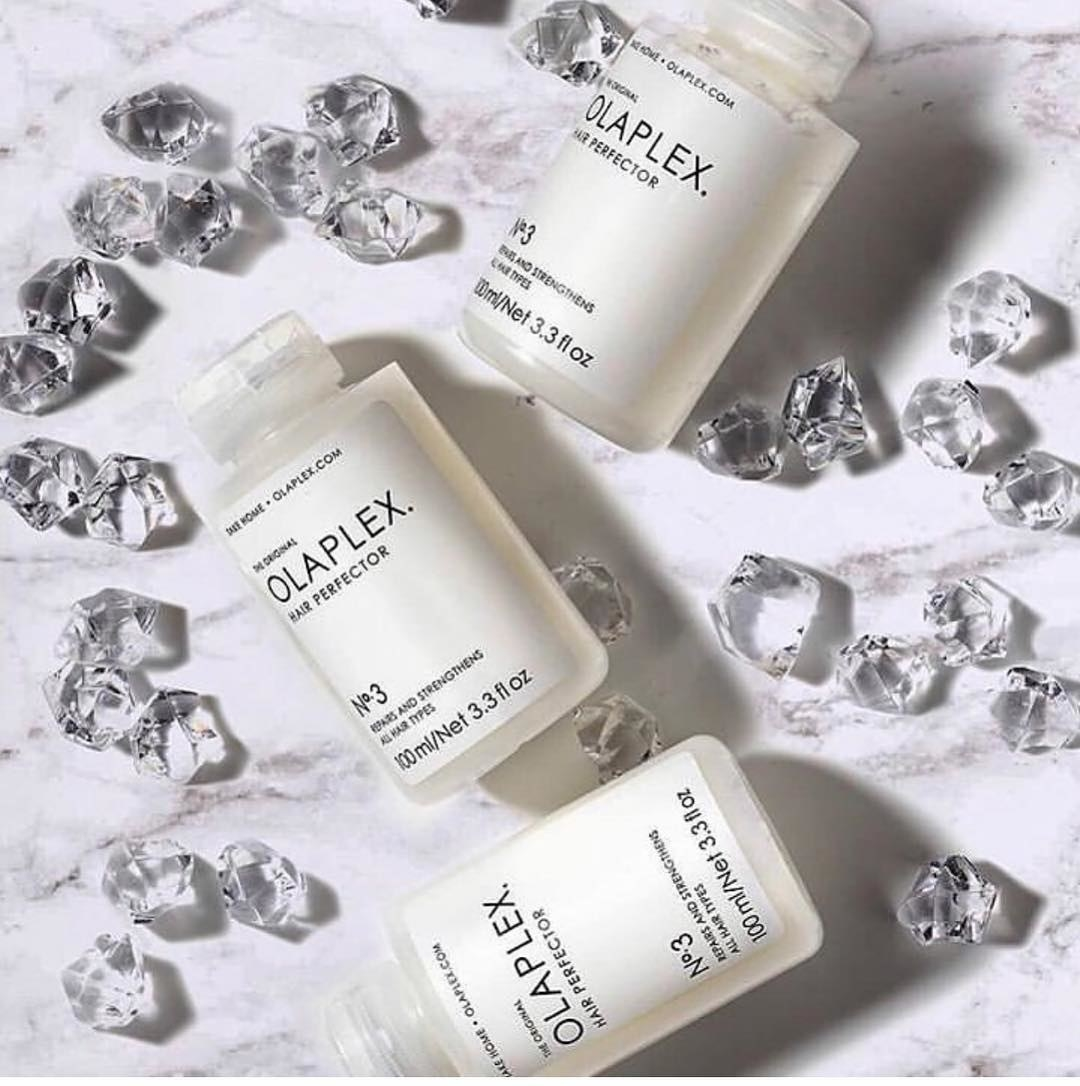 Bottles of the Olaplex Hair Perfector laid out on a marble table