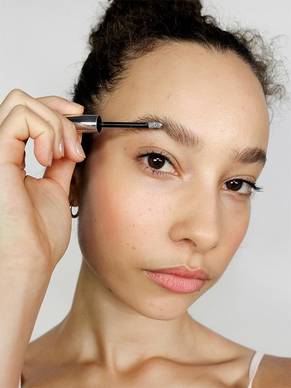 Model using the transparent gel on their brows to fluff and define