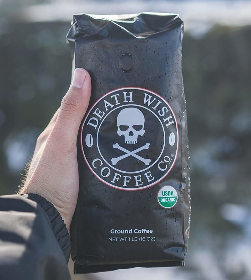 hand holding bag of coffee with skull and crossbones on it