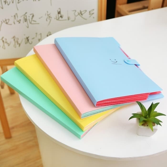 pastel blue, pink yellow, and green accordion folders with one little smiley face on them