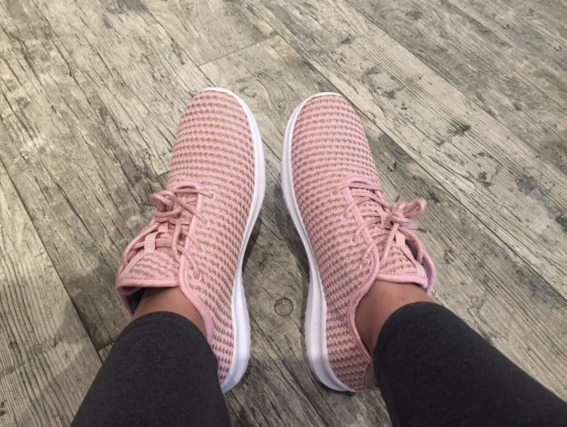 Reviewer's feet wearing the knit sneakers in pink with a white sole