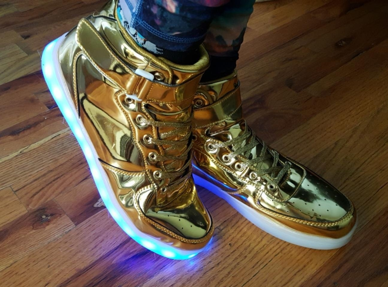 Reviewer wearing the high-top sneakers in shiny gold with a stripe of LED lights around the sole