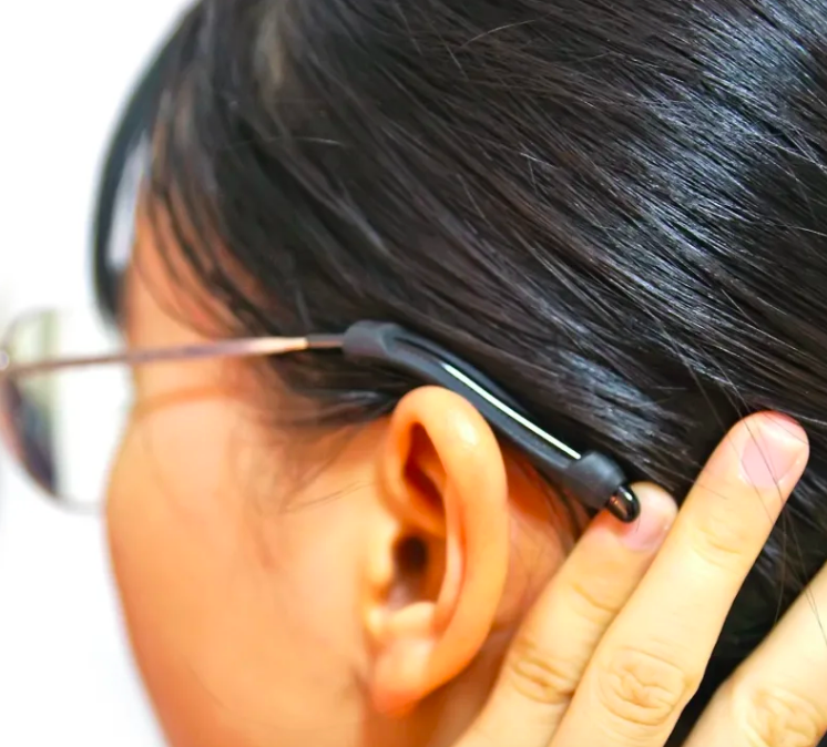 A person with the silicone tip placed through the leg of their glasses, right above their ear