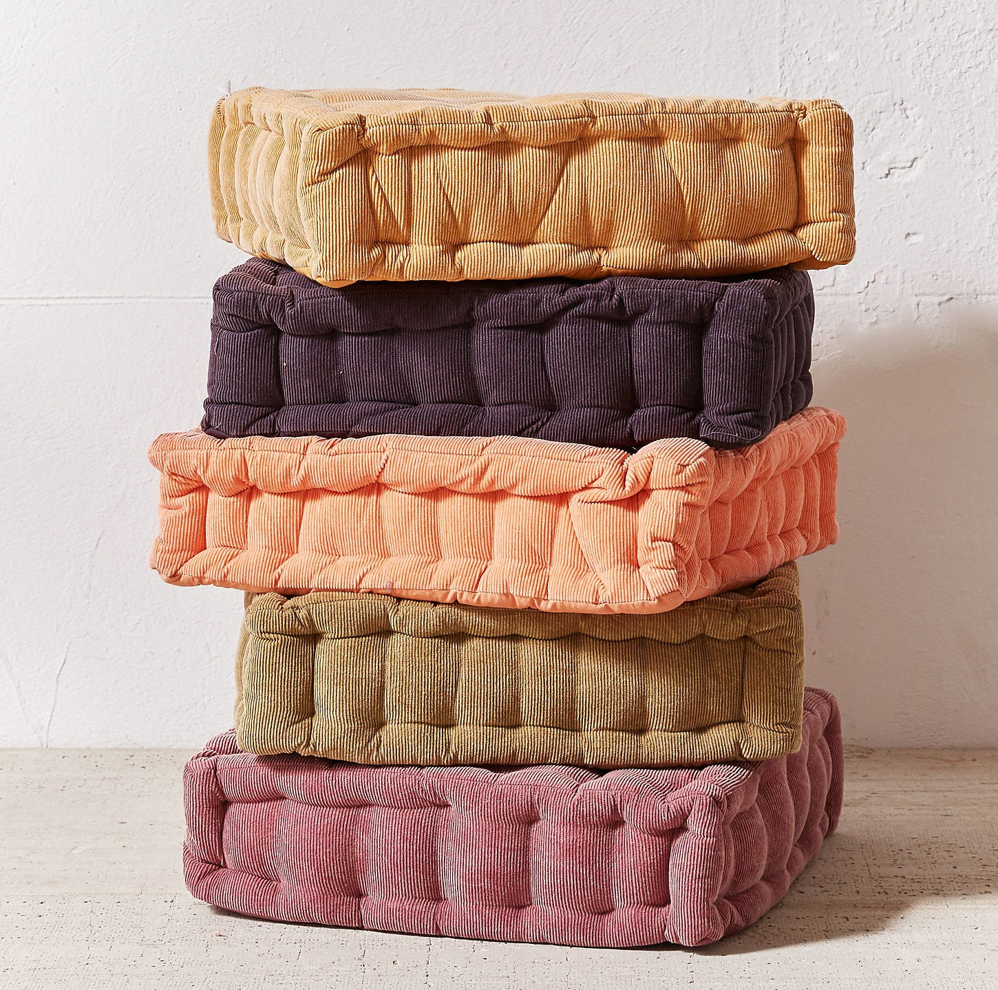 a stack of the square floor pillows in shades of purple, brown, and coral