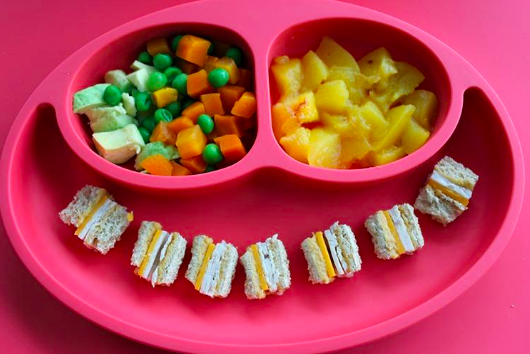 A reviewer showing the three divided sections of the placemat. Two are small and round for chopped sides and one is a long section in the middle for sandwiches and larger foods.