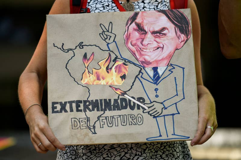 Luis Robayo / AFP / Getty Images An activist at the Brazilian consulate in Cali, Colombia, holds a sign reading, 'Exterminator of the Future' on Aug. 23.