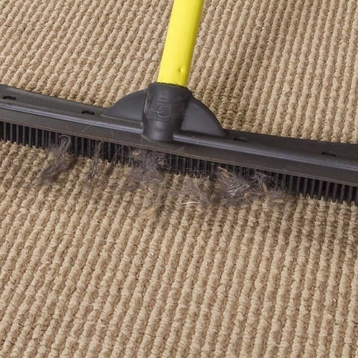 broom picking up hair from low-pile carpet