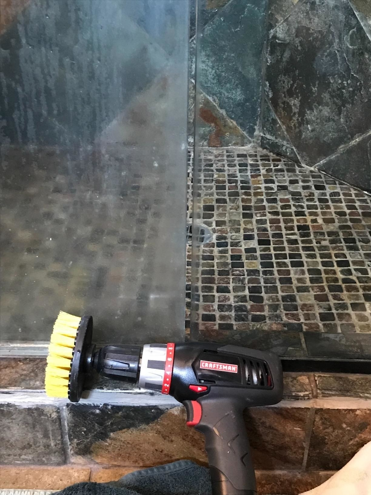 A drill with the three-inch brush attached sitting next to one panel of a shower door that's dirty and caked with buildup and soap scum; and another panel that's completely clean and transparent