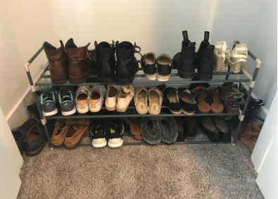 a reviewer's photo of their shoes neatly organized on the three-tiered rack