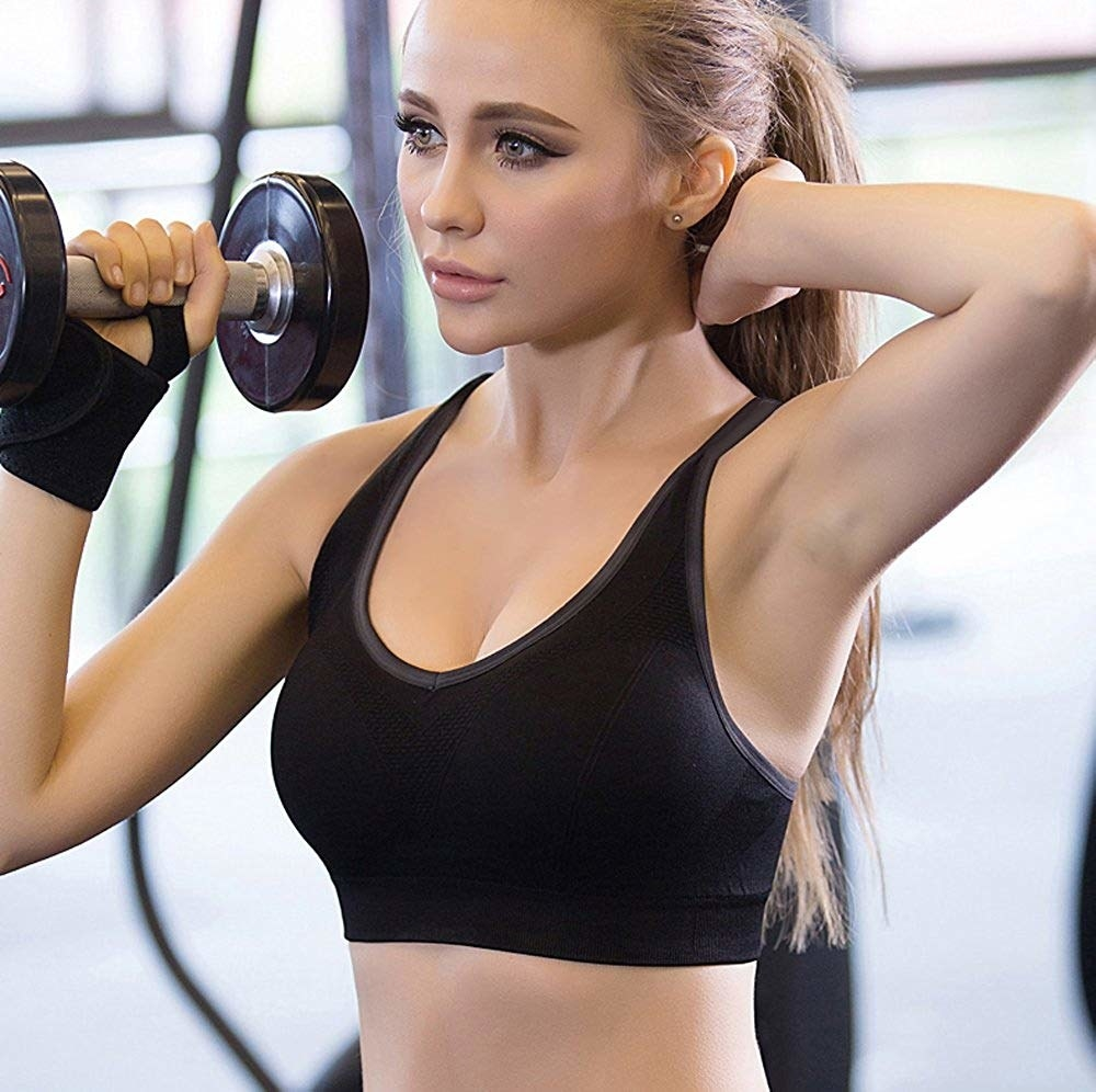 model wearing sports bra and lifting a weight