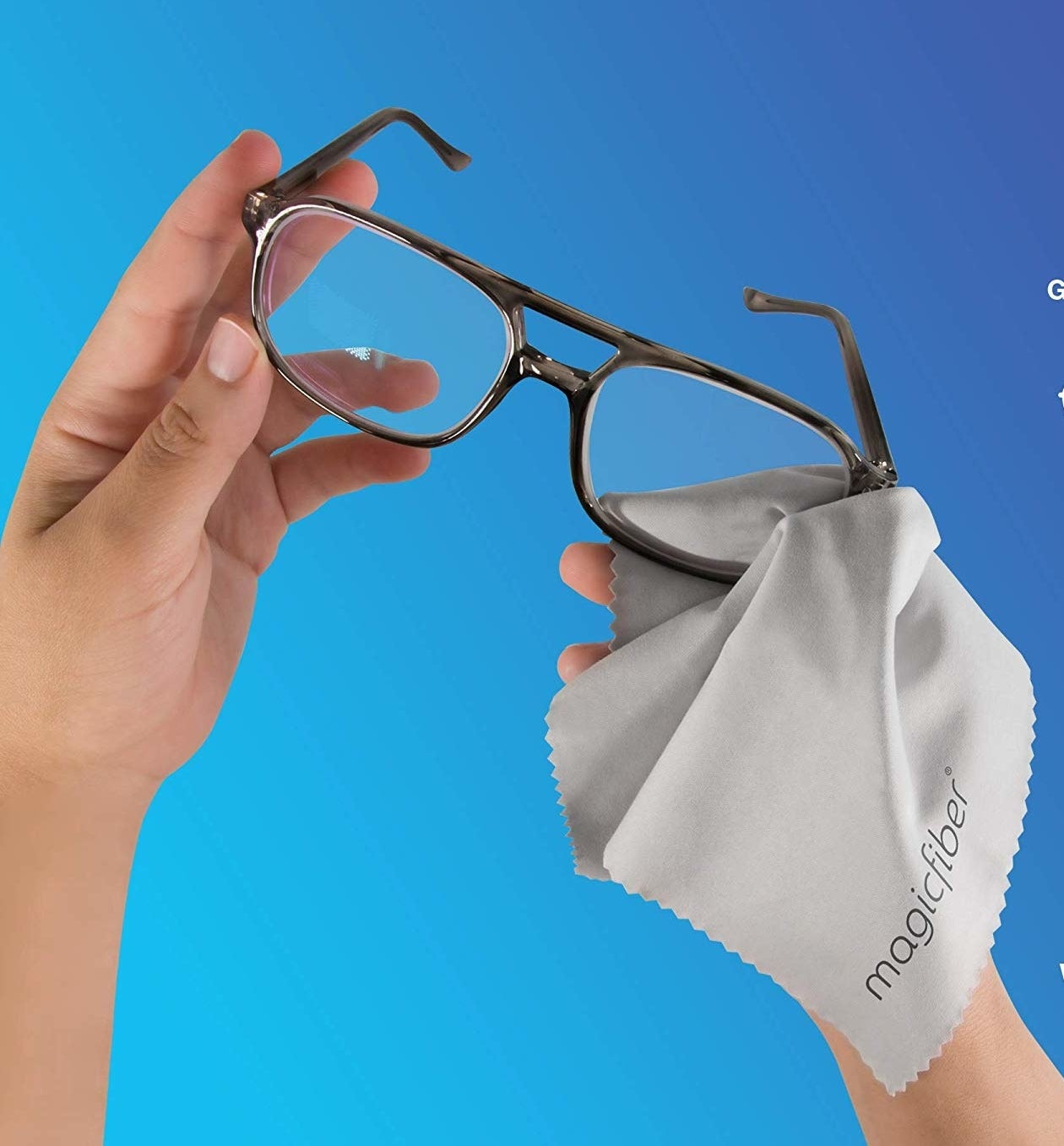 person cleaning glasses with microfiber cloth