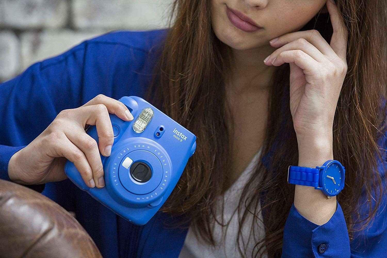 model holds blue camera