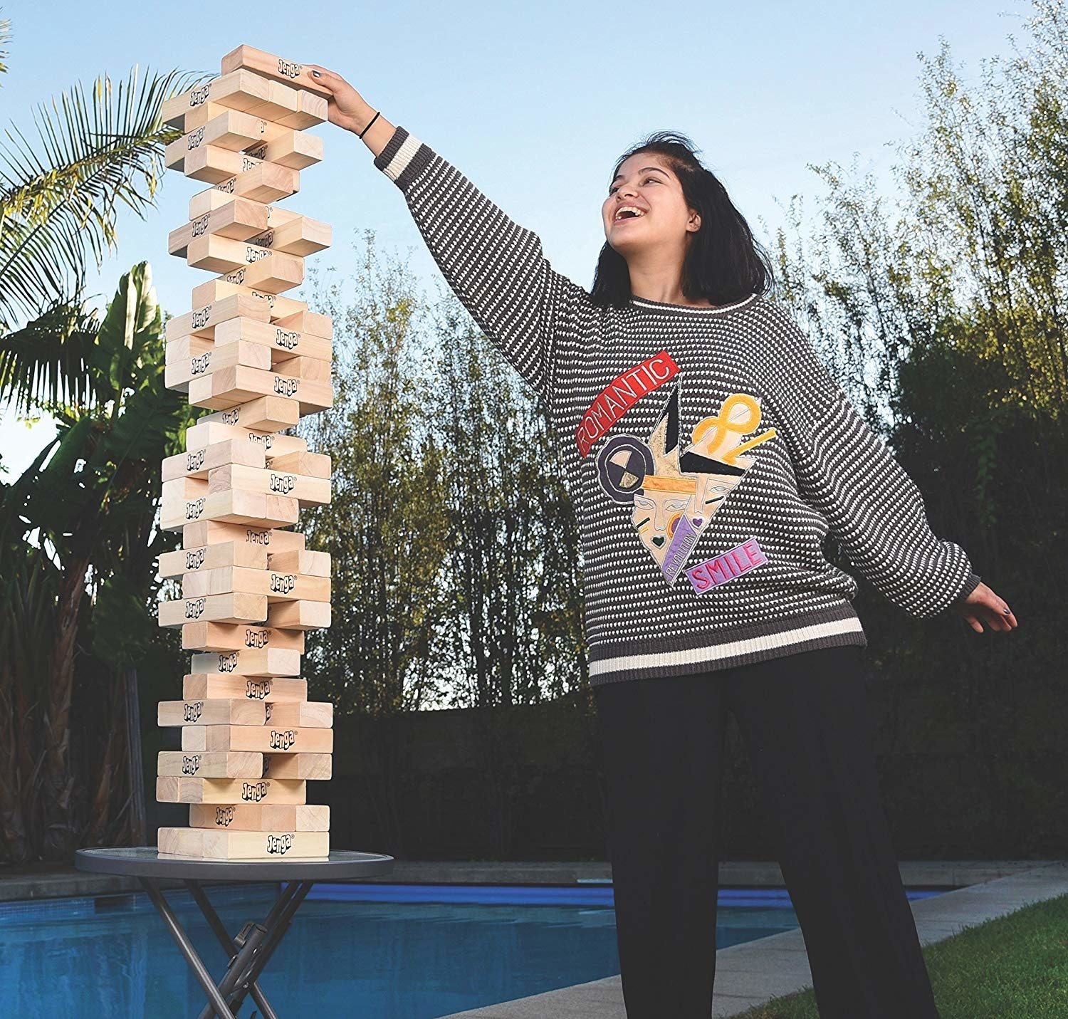 A person playing Jenga that has been put on a small table. With the help of the table, game towers over her head