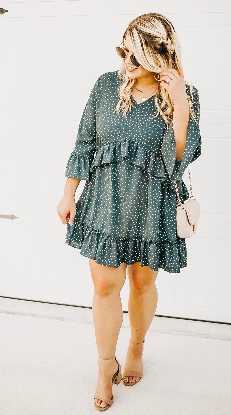 Reviewer wearing a sea foam colored polka dot dress