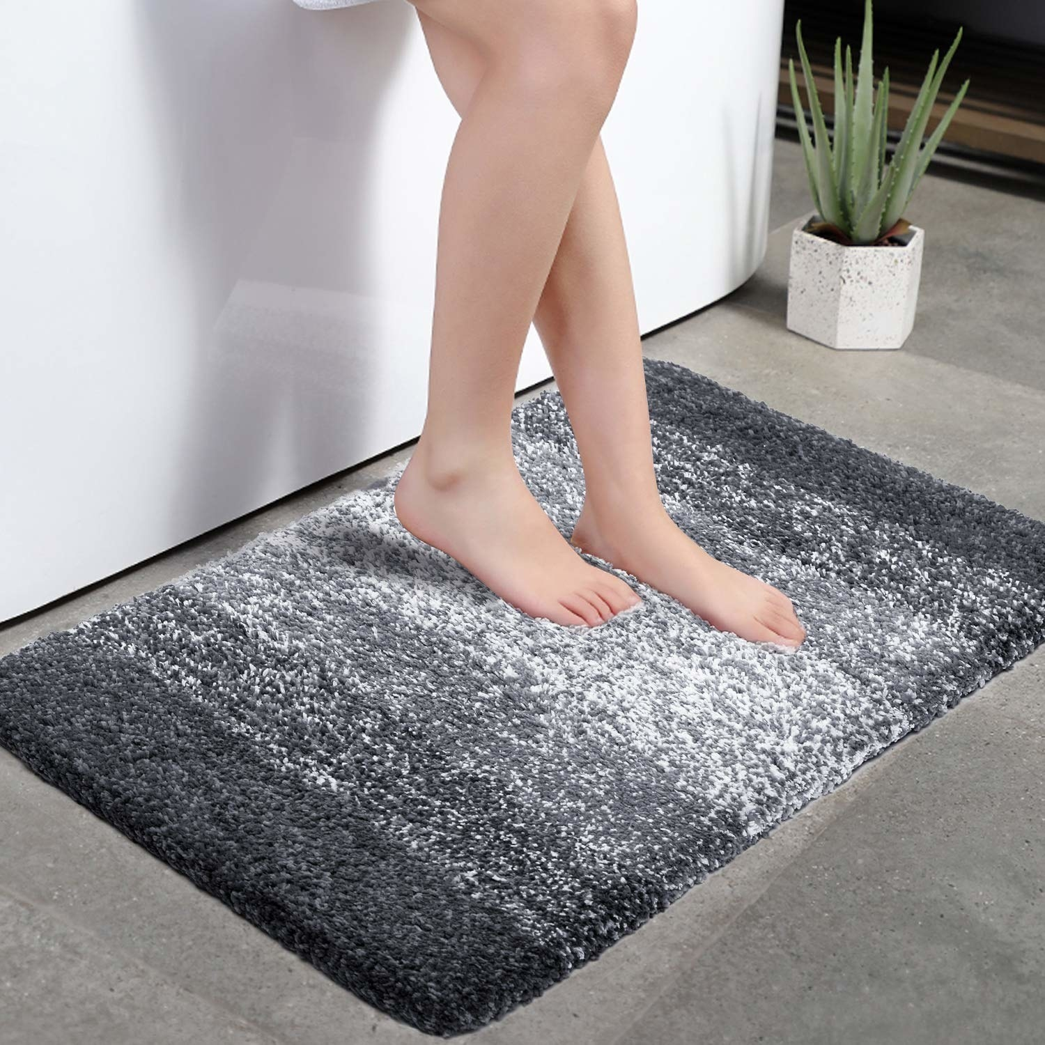 product image of someone putting their feet on a black and white gradient bathmat in front of a shower