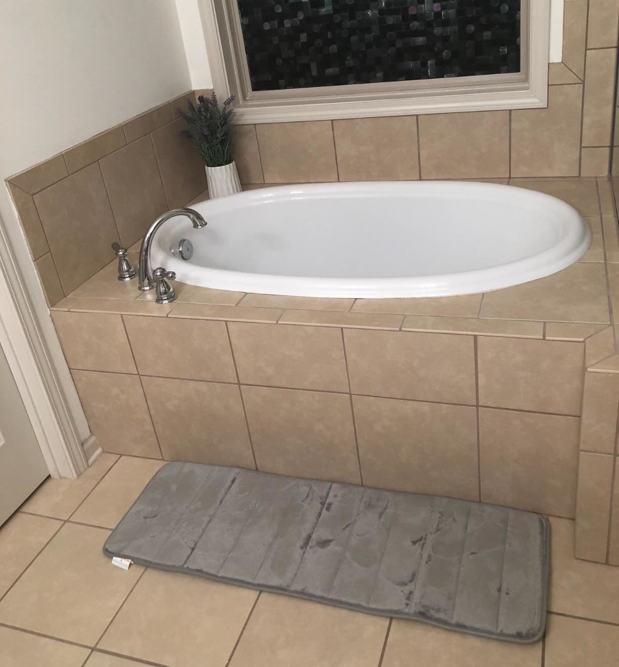 reviewer photo of the bath mat in gray in front of a bathtub