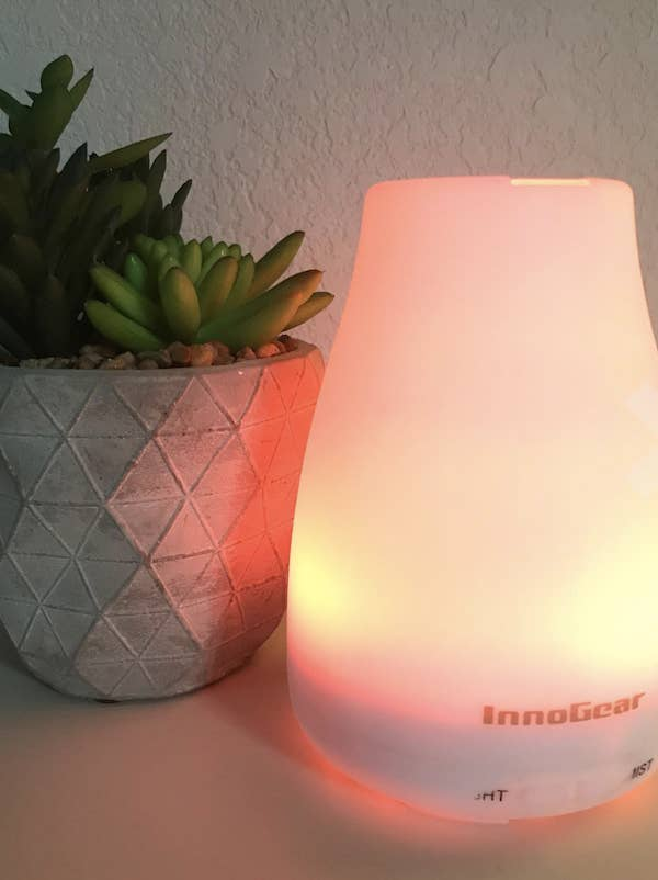A plastic white humidifier is lit with an orange light. It's sitting next to a green succulent in a grey ceramic pot.