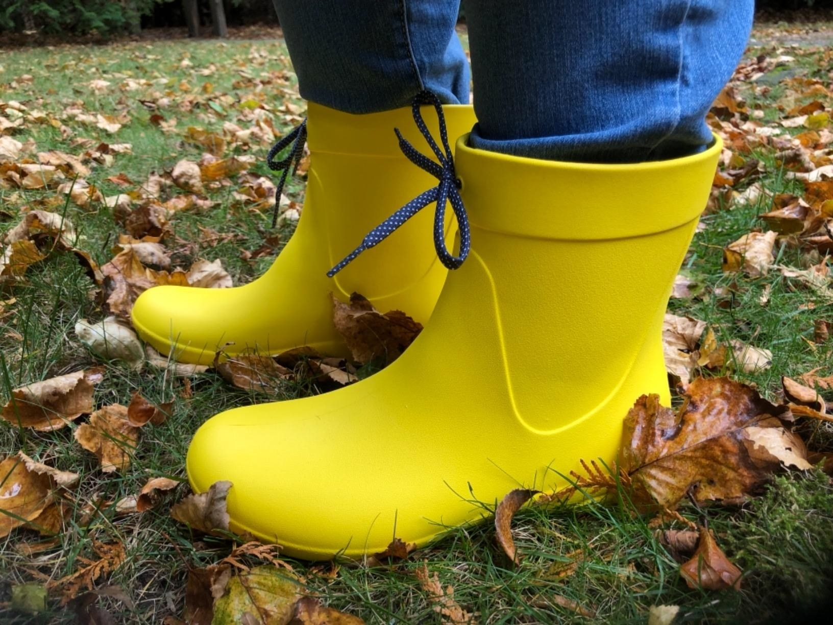 reviewer wearing bright yellow above-the-ankle single-piece boots