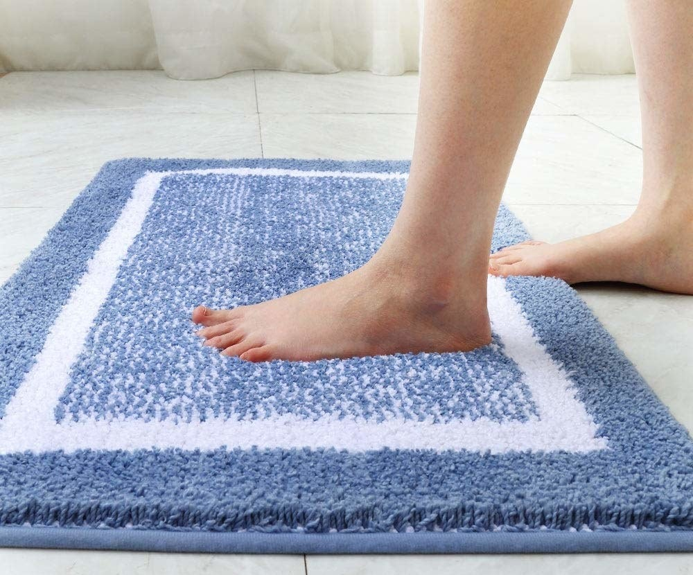 lifestyle image of someone stepping on the bath mat in blue