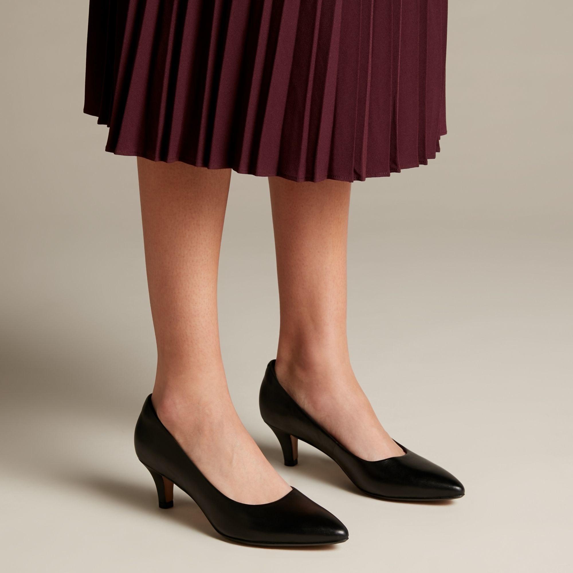 model wearing closed almond-toe black heels