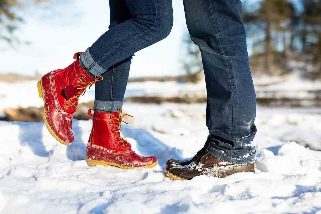 two model's feet in the snow, one in a red pair and one a brown pair of the same high-top boot; there's rubber around the toes and bottom third of the shoes