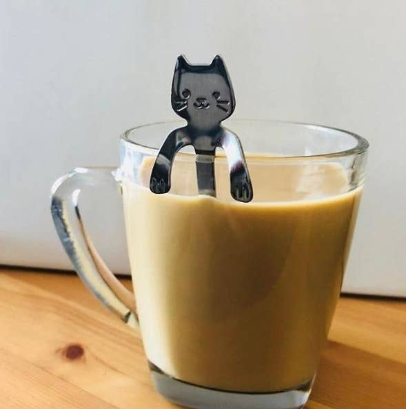 The spoon shaped like a cat sitting inside a coffee mug with its paws hanging over the side of the cup