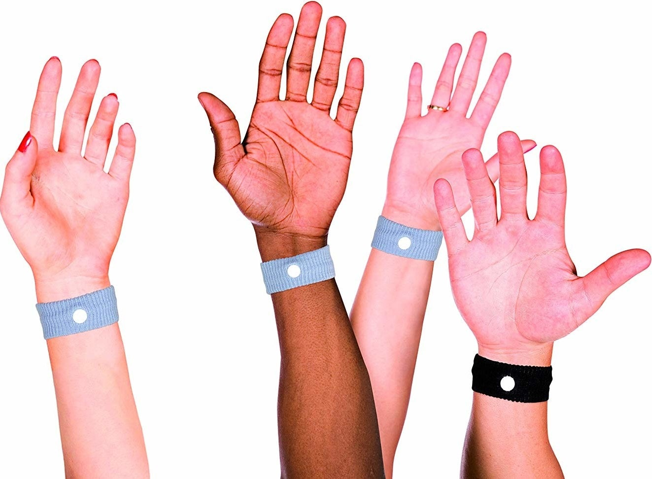 A variety of hands wearing the anti-nausea wristband.