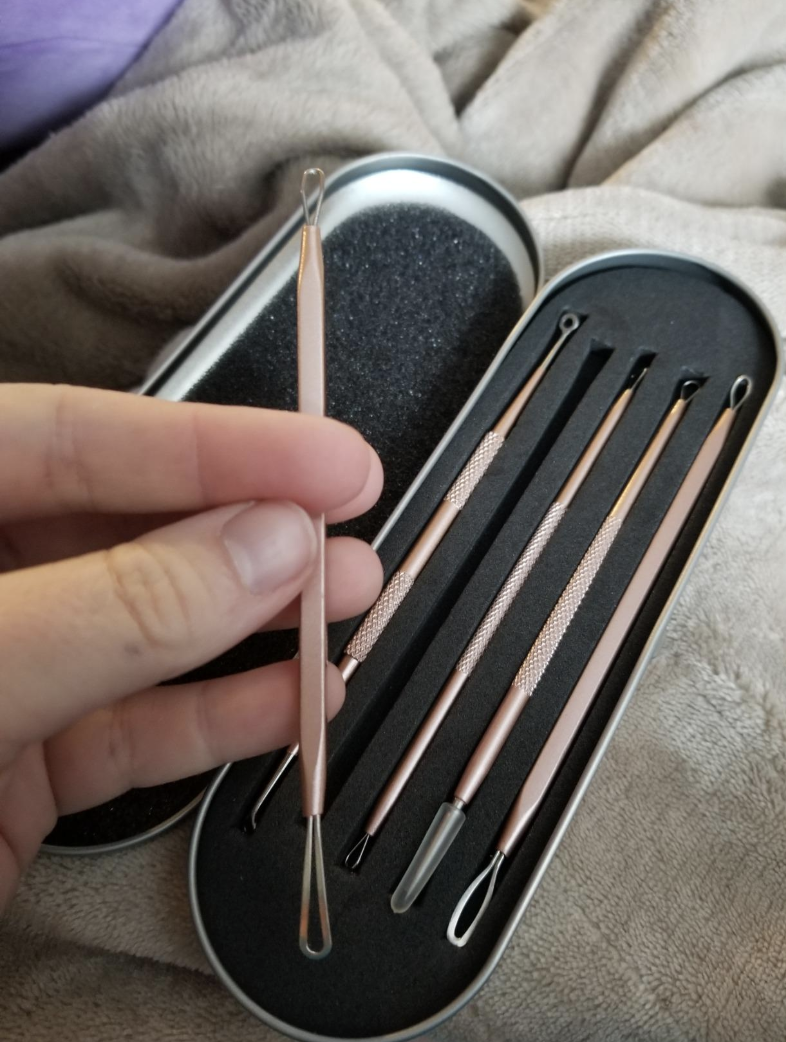 A silver tin (shaped like an eyeglass case) is black on the inside and has five skinny slots where the blackhead remover tools are sitting. A hand is holding one of the tools which has a looped end.