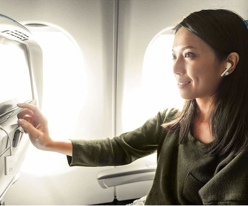 model with wireless ear buds on plane