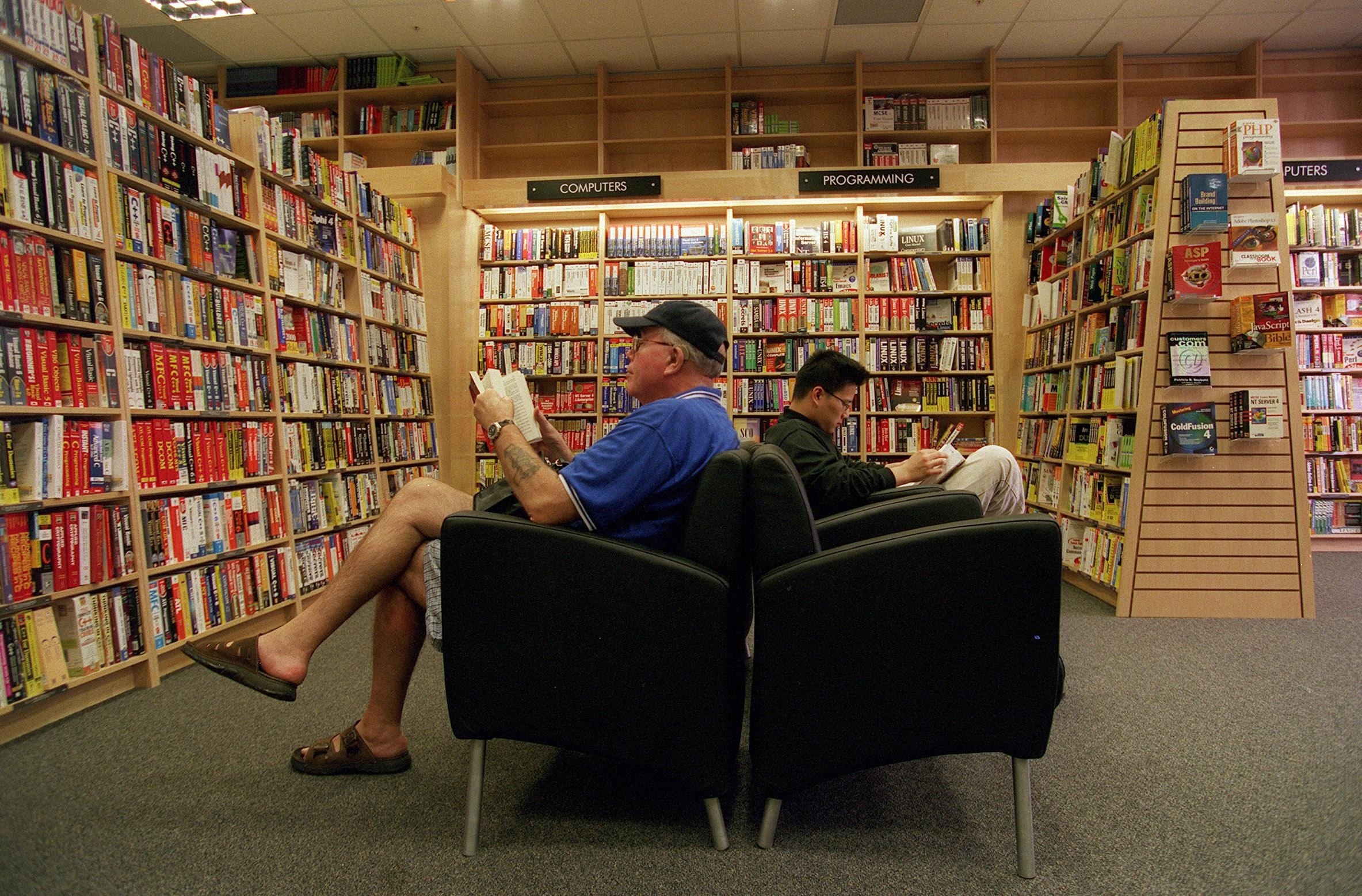 Two men sitting in chairs inside a Borders reading books