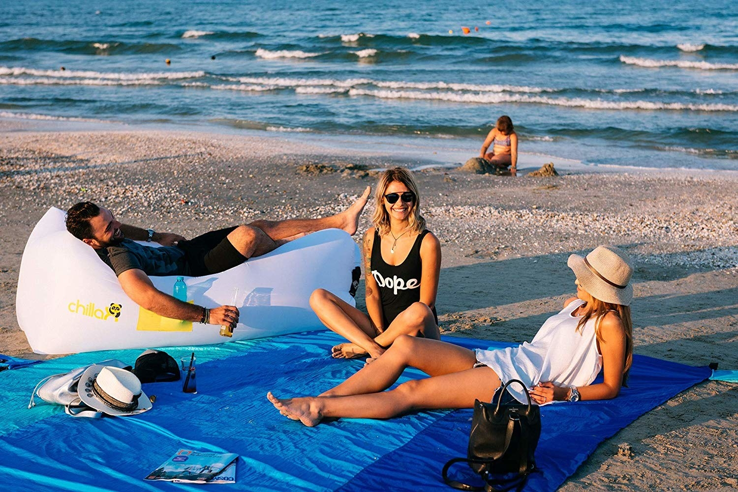 models sitting on a multi-colored blue blanket on a beach