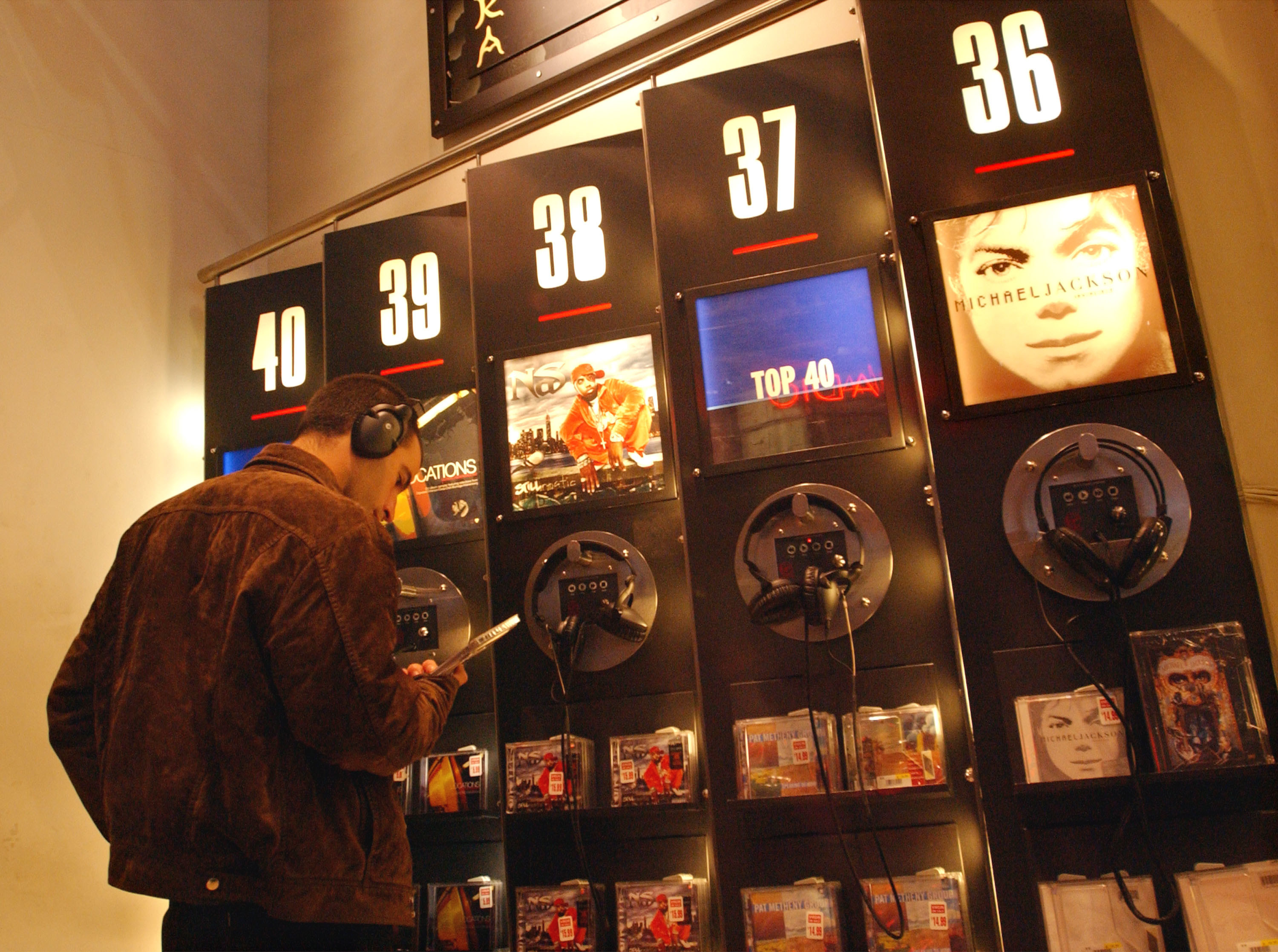 A man listening to a CD while at a CD kiosk in the Virgin Megastore