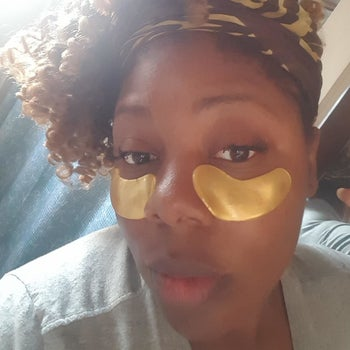 reviewer wearing the gold eye pads