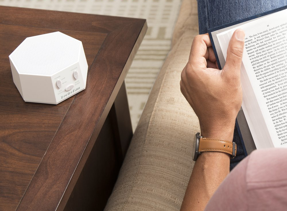 A white hexagon shaped noise machine on a table
